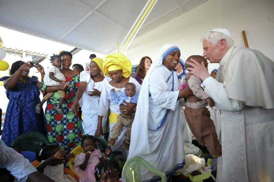 "Pope Benedict XVI arrives surrounded by children at St. Rita's Parish in Cotonou on November 19, 2011. Pope Benedict XVI arrived in Benin on November 18, marking his second visit to Africa in a heartland of voodoo and warning against ""unconditional submission"" to the laws of the market and finance. Photo: OSSERVATORE ROMANO, Getty / AFP"
