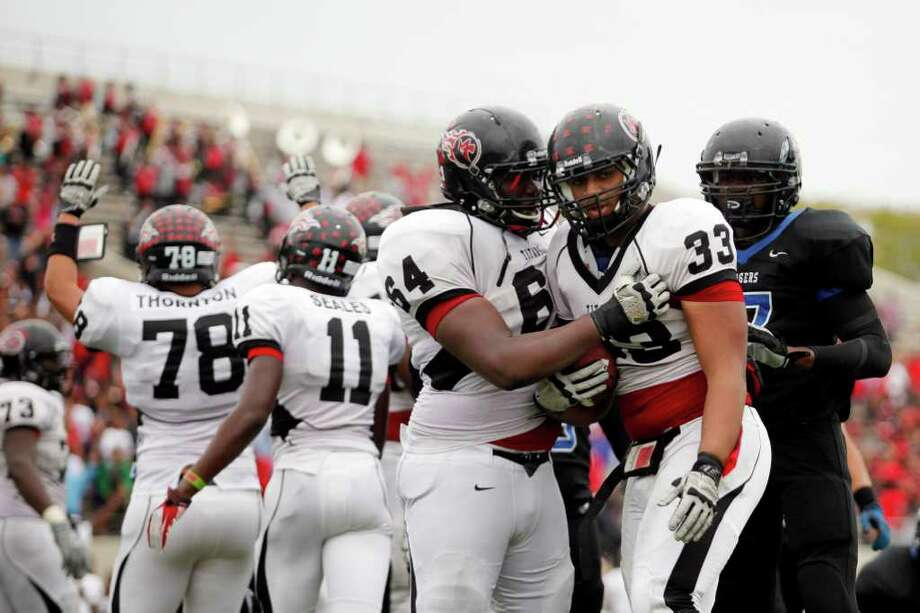 Memorial junior, Matthew Romar, 33, if congratulated by offensive lineman, Johnathan Ned, 64, following a goal line touchdown, during the second half of a high school football playoff game between the Clear Springs High School Chargers and the Port Arthur Memorial Titans, Saturday, November 19, 2011 at Stallworth Stadium in Baytown, Texas. PA Memorial won 38-35. (Todd Spoth / For The Chronicle) Photo: TODD SPOTH, Photographer / Todd Spoth