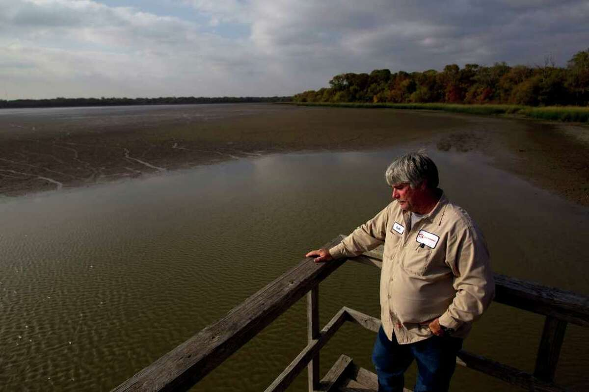 With just a small patch of water left, Keith Tilley, 50, the City of Groesbeck's director of public works, looks out onto the dried out 700 acre Fort Parker Lake, one of the sources of water that feeds the Navasota River, the city's main water source Wednesday, Nov. 16, 2011, in Groesbeck.