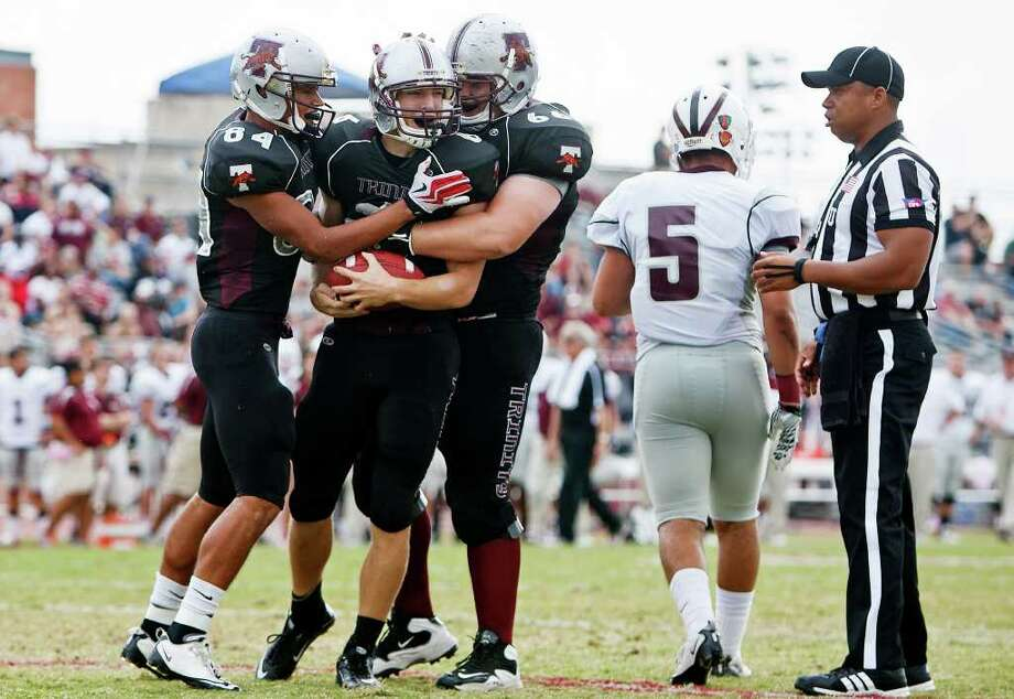 Trinity's Hagen Kattner (left) and Conner Cox celebrate with Matthew Kennemer after Kennemer's first quarter touchdown reception to open the scoring  in their NCAA Division III first-round playoff game with McMurry at Trinity University Stadium on Nov. 19, 2011.  McMurry advanced to the next round of the playoffs with a 25-16 victory over the Tigers.  MARVIN PFEIFFER/mpfeiffer@express-news.net Photo: MARVIN PFEIFFER, Express-News / Express-News 2011