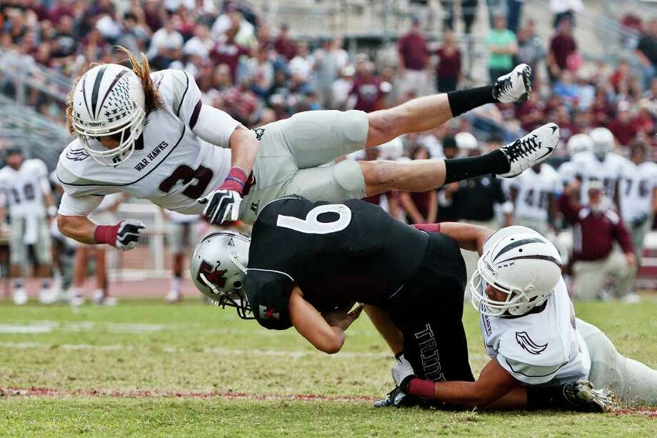 McMurry defensive back Will Morris flies over Trinity wide receiver Matthew Kennemer (center) as Kennemer crosses the goal line for a touchdown while being tackled by M.D. Daniels during the first quarter of their NCAA Diivision III first-round playoff game at Trinity University Stadium on Nov. 19, 2011.  McMurry advanced to the next round of the playoffs with a 25-16 victory over the Tigers.  MARVIN PFEIFER/mpfeiffer@express-news.net Photo: MARVIN PFEIFFER, Express-News / Express-News 2011