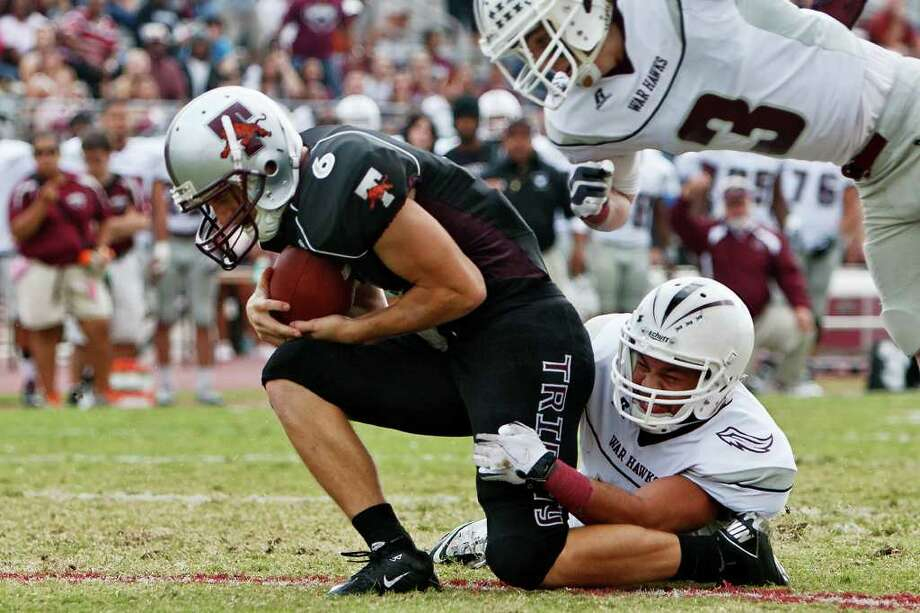 Trinity wide receiver Matthew Kennemer (left) crosses the goal line for a touchdown despite the efforts of McMurry's M.D. Daniels and Will Morris (right) during the first quarter of their NCAA Diivision III first-round playoff game at Trinity University Stadium on Nov. 19, 2011.  McMurry advanced to the next round of the playoffs with a 25-16 victory over the Tigers.  MARVIN PFEIFER/mpfeiffer@express-news.net Photo: MARVIN PFEIFFER, Express-News / Express-News 2011