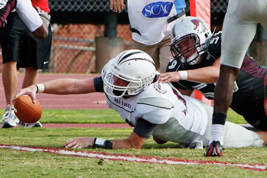 McMurray quarterback Stephen Warren reaches the ball across the goal line for a two-point conversion despite the efforts of Trinity's Joshua Cavazos during the third quarter of their NCAA Division III first-round playoff game at Trinity University Stadium on Nov. 19, 2011.  McMurry advanced to the next round of the playoffs with a 25-16 victory over the Tigers.  MARVIN PFEIFFER/mpfeiffer@express-news.net Photo: MARVIN PFEIFFER, Express-News / Express-News 2011