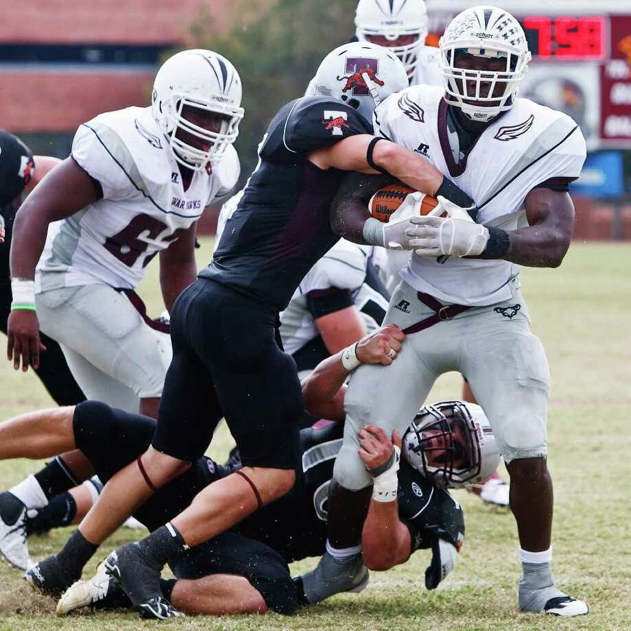 Trinity's Tyler Barrett (center) and Nick Darling (below) combine to bring down McMurry running back Justin Johnson during the second quarter of their NCAA Division III first-round playoff game at Trinity University Stadium on Nov. 19, 2011.  McMurry advanced to the next round of the playoffs with a 25-16 victory over the Tigers.  MARVIN PFEIFFER/mpfeiffer@express-news.net Photo: MARVIN PFEIFFER, Express-News / Express-News 2011