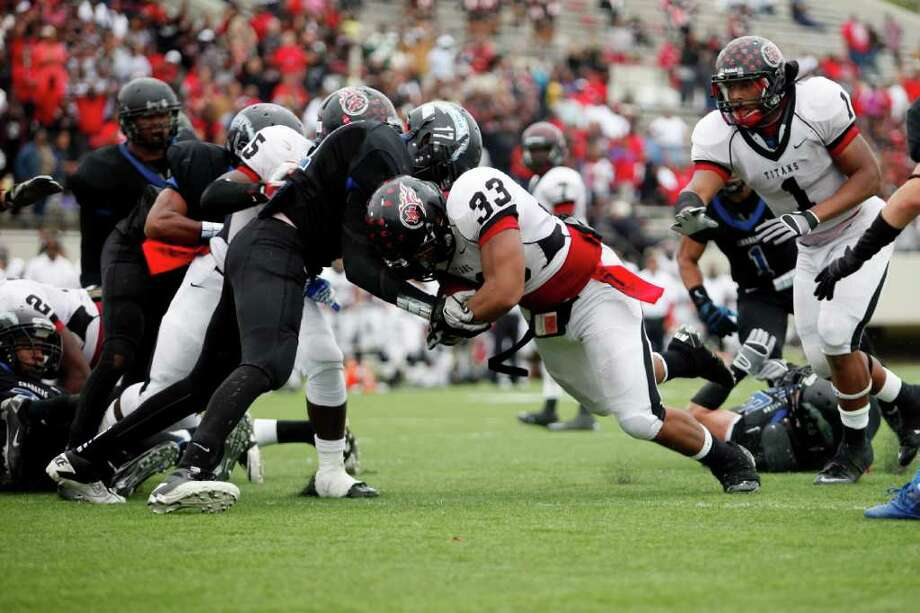 Memorial junior, Matthew Romar, 33, pushes through the defense for a goal line touchdown, during the second half of a high school football playoff game between the Clear Springs High School Chargers and the Port Arthur Memorial Titans, Saturday, November 19, 2011 at Stallworth Stadium in Baytown, Texas. PA Memorial won 38-35. Photo: TODD SPOTH, For The Chronicle / Todd Spoth