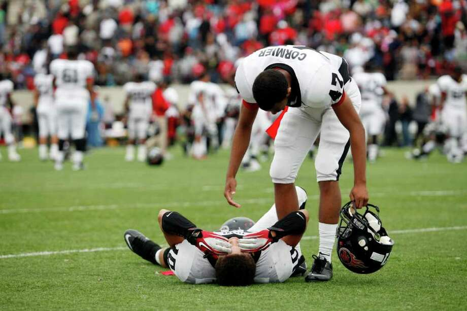 Memorial junior, James Jenkins, 10, is helped up by senior, Bryce Cormier, 47, as he lays on the field in reflection, following a high school football playoff game between the Clear Springs High School Chargers and the Port Arthur Memorial Titans, Saturday, November 19, 2011 at Stallworth Stadium in Baytown, Texas. PA Memorial won 38-35. Two Memorial players suffered injuries which included heat exhaustion and had to be taken off the field by EMT's. Photo: TODD SPOTH, For The Chronicle / Todd Spoth
