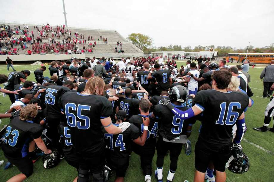 Both teams join in prayer for their injured teammates, following a high school football playoff game between the Clear Springs High School Chargers and the Port Arthur Memorial Titans, Saturday, November 19, 2011 at Stallworth Stadium in Baytown, Texas. PA Memorial won 38-35. Two Memorial players suffered injuries which included heat exhaustion and had to be taken off the field by EMT's. Photo: TODD SPOTH, For The Chronicle / Todd Spoth