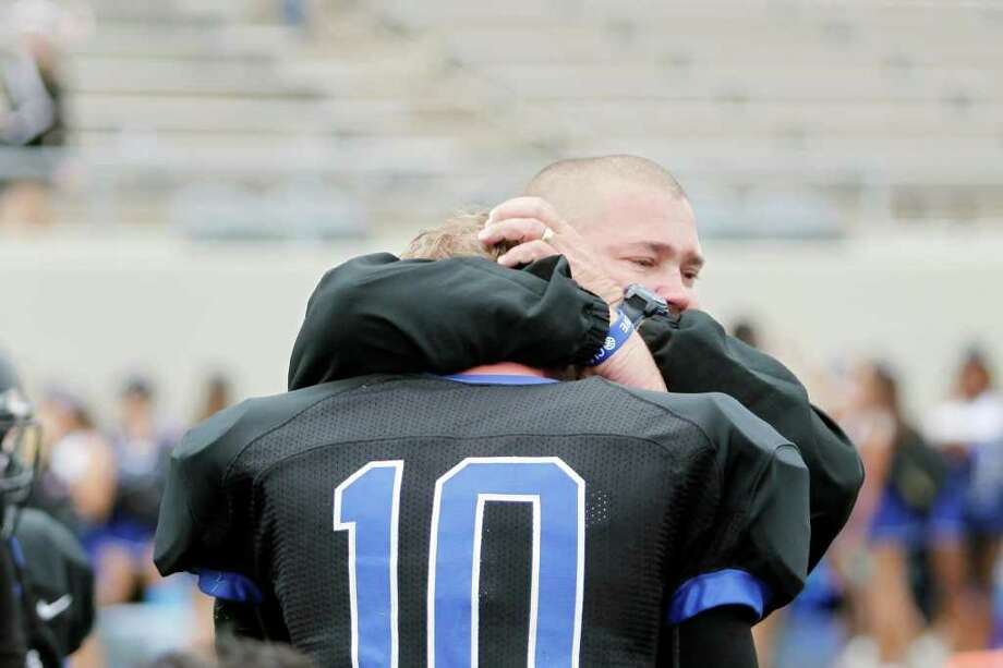 Clear Springs head coach, Clint Hartman, embraces junior quarterback, Jake Blackledge, 10, following a high school football playoff game between the Clear Springs High School Chargers and the Port Arthur Memorial Titans, Saturday, November 19, 2011 at Stallworth Stadium in Baytown, Texas. PA Memorial won 38-35. Photo: TODD SPOTH, For The Chronicle / Todd Spoth