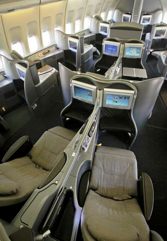 This Oct. 28, 2011 photo shows the new first class interior section of a United Airlines 747 plane at San Francisco International Airport in San Francisco. U.S. airlines are spending nearly $2 billion to upgrade long-neglected lounges and aircraft. Their most-prized customers are getting new seats that turn into beds, large flat-screen TVs and savory food and wine. (AP Photo/Tony Avelar) Photo: Tony Avelar