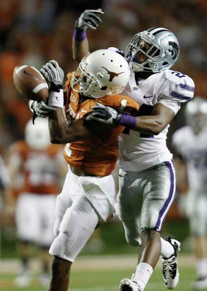 Texas' Mike Davis is defended by Kansas State's Nigel Malone, right, as he tries to make a catch
