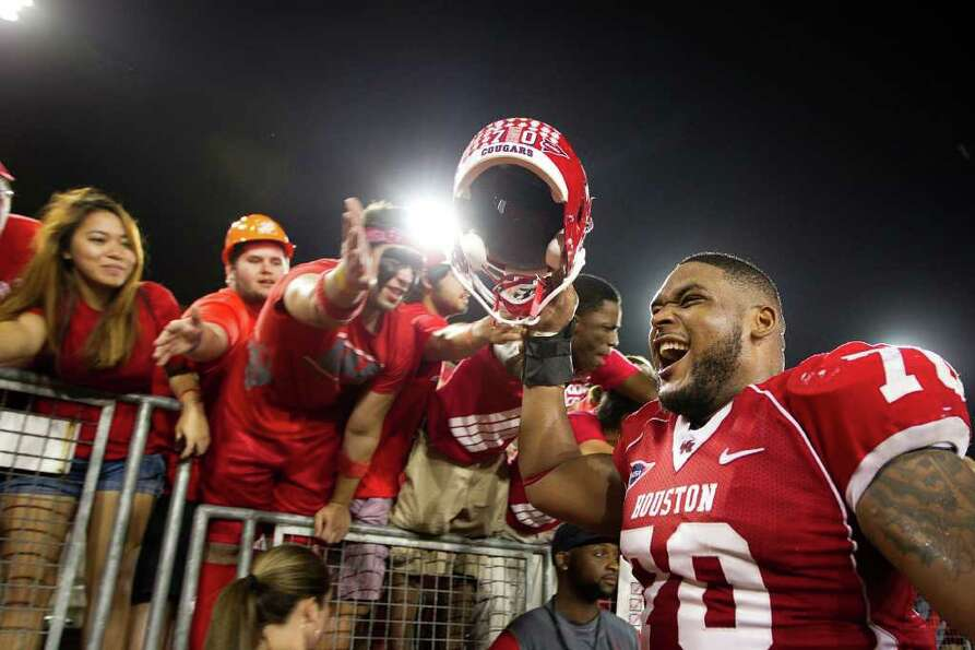 Houston offensive linesman Chris Thompson celebrates with fans after the Cougars defeated SMU 37-7.