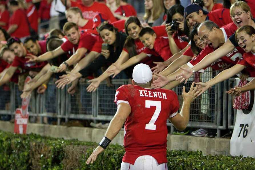 Houston quarterback Case Keenum celebrates with fans after the Cougars defeated SMU.