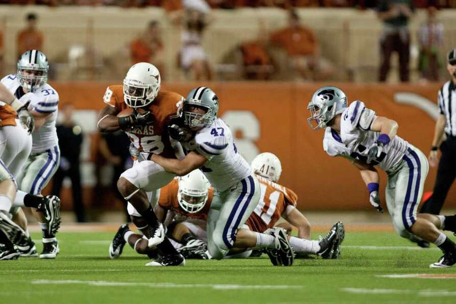 AUSTIN, TX - NOVEMBER 19:  Jared Loomis #47 of Kansas State Wildcats tackles Malcolm Brown #28 of th