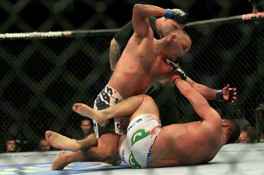 Dan Henderson, top, punches Mauricio Rua, from Brazil, during the fourth round of a UFC 139 Mixed Martial Arts light heavyweight bout in San Jose, Calif., Saturday, Nov. 19, 2011. Henderson won by unanimous decision. (AP Photo/Jeff Chiu) Photo: Jeff Chiu, Associated Press / AP