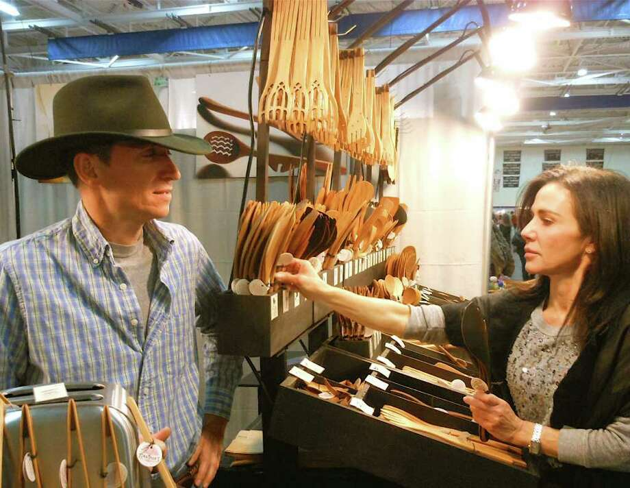 Stephanie Fasone, of Westport, checks out wooden spoons made by Jonathan Simons, left, at 36th annual CraftWEstport on Saturday at Staples High School. Fasone sports a scarf made by another vendor, Karen Ford. Photo: Mike Lauterborn / Westport News contributed
