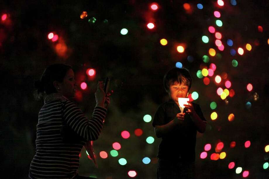 FOR METRO - Maricela Garcia-Gallegos (left) photographs her son Rafael Garcia-Gallegos, 5, while attending the University of the Incarnate Word's 25th Annual Light the Way celebration held Saturday Nov. 19, 2011 on the campus. (PHOTO BY EDWARD A. ORNELAS/eaornelas@express-news.net) Photo: EDWARD A. ORNELAS, SAN ANTONIO EXPRESS-NEWS / © SAN ANTONIO EXPRESS-NEWS (NFS)