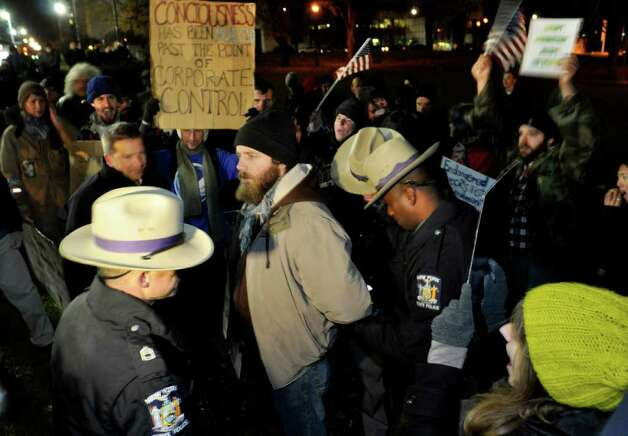 Andrew Kenwick, an Occupy Albany protester, faces off with New  York State Troopers moments before he was arrested, along with several   other protesters who violated an 11 p.m. curfew in state-run Lafayette   Park, which is located across Washington Avenue from the state  Capitol  in Albany on Saturday, Nov. 19, 2011. Photo: Stewart Cairns, AP / FR112526AP