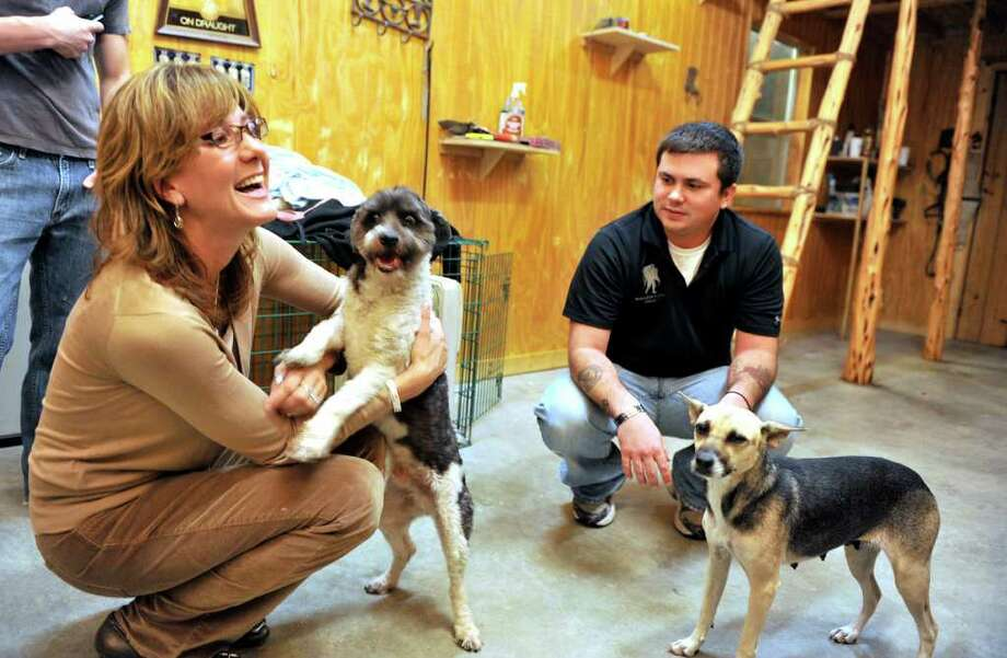Former Army Cpl. Kacey Schlundt (right) and Tracy Voss, founder of La Vernia-based canine rescue organization Tracy's Dogs, play with dogs that Schlundt will transport to new owners. Photo: ROBIN JERSTAD, FOR THE EXPRESS-NEWS