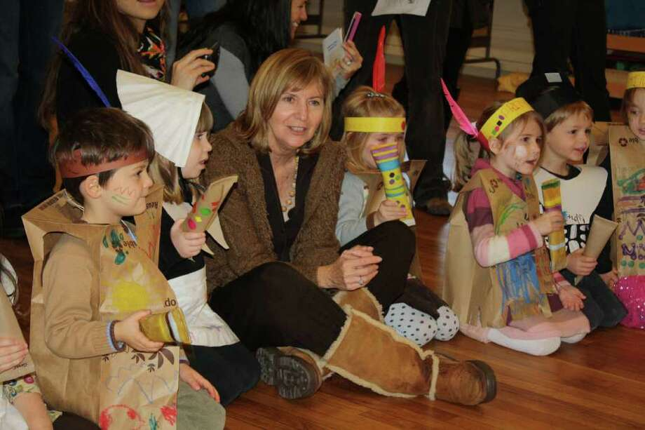 """Greens Farms Nursery School teacher Patty Gatto is surrounded by Native Americans and Pilgrims during a Thanksgiving observation by the school's """"big kids,"""" the 4 year olds. Photo: Contributed Photo / Westport News contributed"""