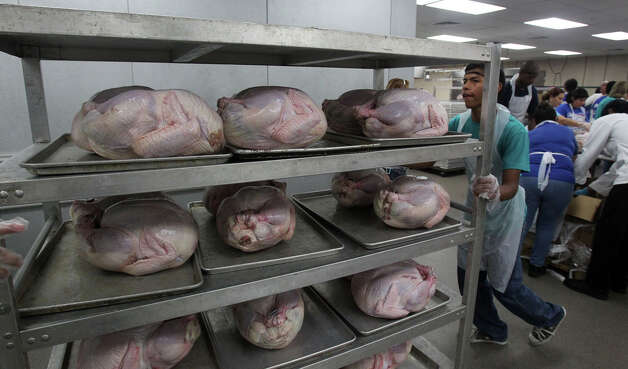 Mero Martinez, 13, pushes a cart full of turkeys into a walk-in cooler, Nov. 20, 2011, at the Convention Center.  Photo: JOHN DAVENPORT, SAN ANTONIO EXPRESS-NEWS / SAN ANTONIO EXPRESS-NEWS (Photo can be sold to the public)
