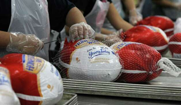 Volunteers unwrap turkeys Nov. 20, 2011, at the Convention Center in preparation for the annual Raul Jimenez Thanksgiving Dinner.  Photo: SAN ANTONIO EXPRESS-NEWS