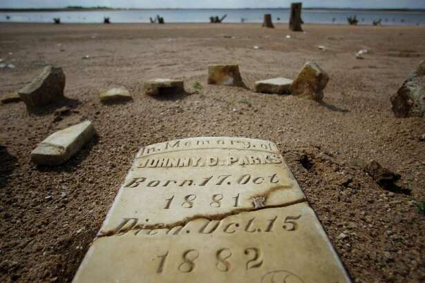 In this Oct. 5, 2011 photo, a child's grave site, normally at least 20 to 30 feet underwater, has joined other remnants of old Bluffton, Texas, resurfacing on the now dry, sandy lake near Bluffton, as the Texas drought shrinks the state's largest inland lake.