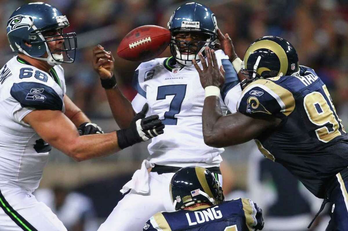 ST. LOUIS, MO - NOVEMBER 20: Tarvaris Jackson #7 of the Seattle Seahawks looses control of the ball after being hit by James Hall #96 of the St. Louis Rams at the Edward Jones Dome on November 20, 2011 in St. Louis, Missouri.