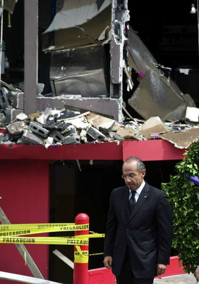 "Mexican President Felipe Calderon walks in front of the Casino Royale, in Monterrey, Mexico, on August 26, 2011. Calderon condemned Friday the ""abhorrent and barbaric"" killing of 52 people by suspected drug cartel gunmen who ruthlessly set a casino ablaze. The particularly callous attack on Thursday evening shocked a nation routinely used to grim murders and high tolls in a drugs war that has claimed more than 41,000 lives since Calderon launched a military crackdown in 2006. Photo: RONALDO SCHEMIDT, AFP/Getty Images / 2011 AFP"