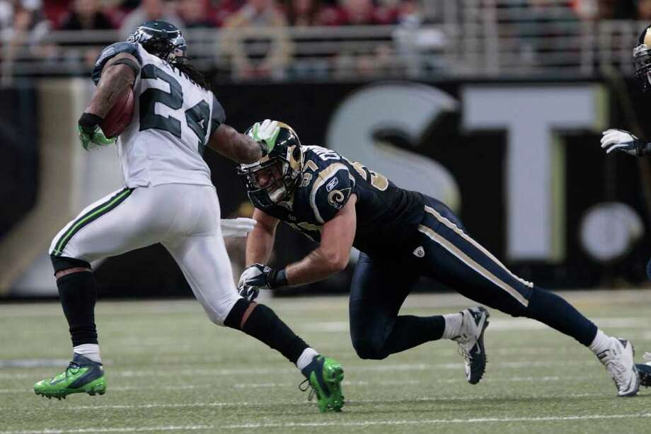 ST. LOUIS, MO - NOVEMBER 20:  Seattle Seahawks running back Marshawn Lynch #24 runs the ball against St. Louis Rams linebacker Chris Chamberlain #57 in the second half of the game November 20, 2011 at the Edward Jones Dome in St. Louis, Missouri. Photo: Whitney Curtis, Getty Images / 2011 Getty Images