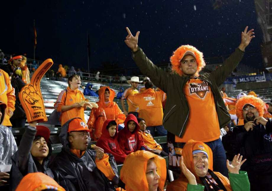 Houston Dynamo fans bundle up against the falling rain before the first half of the MLS Cup soccer match between the Dynamo and the Los Angeles Galaxy at the Home Depot Center Sunday, Nov. 20, 2011, in Carson, Calif. Photo: Brett Coomer, Houston Chronicle / © 2011 Houston Chronicle