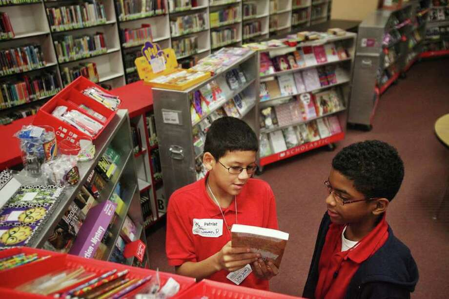 Javan Plummer, 12, shows classmate Devante Valentine, 11, a book he plans to purchase at a book fair at Revere Middle School on Wednesday. Money generated during the Scholastic book fair will benefit the library. Photo: Mayra Beltran / © 2011 Houston Chronicle