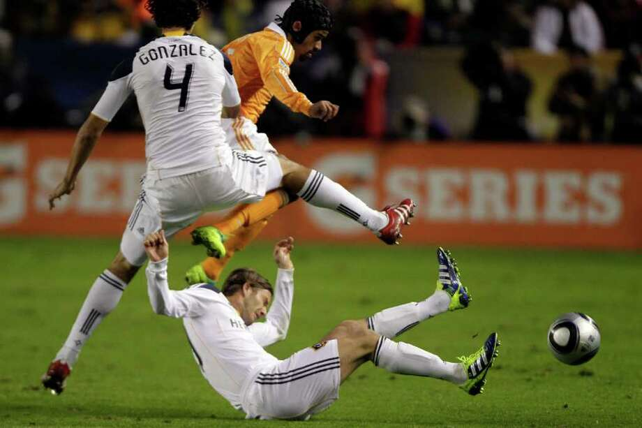Dynamo forward Calen Carr (3) leaps over Los Angeles Galaxy midfielder David Beckham (23) as defender Omar Gonzalez (4) makes contact during the first half of Sunday's MLS Cup match at the Home Depot Center in Carson, Calif. Photo: Brett Coomer, Houston Chronicle / © 2011 Houston Chronicle