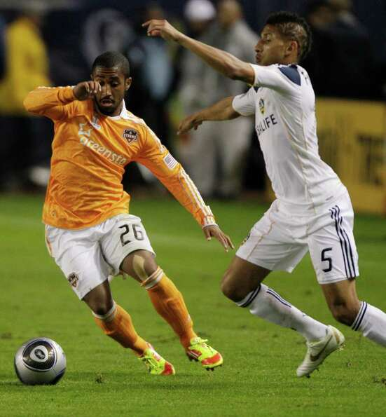 Houston Dynamo midfielder Corey Ashe (26) fights for the ball against Los Angeles Galaxy defender Se