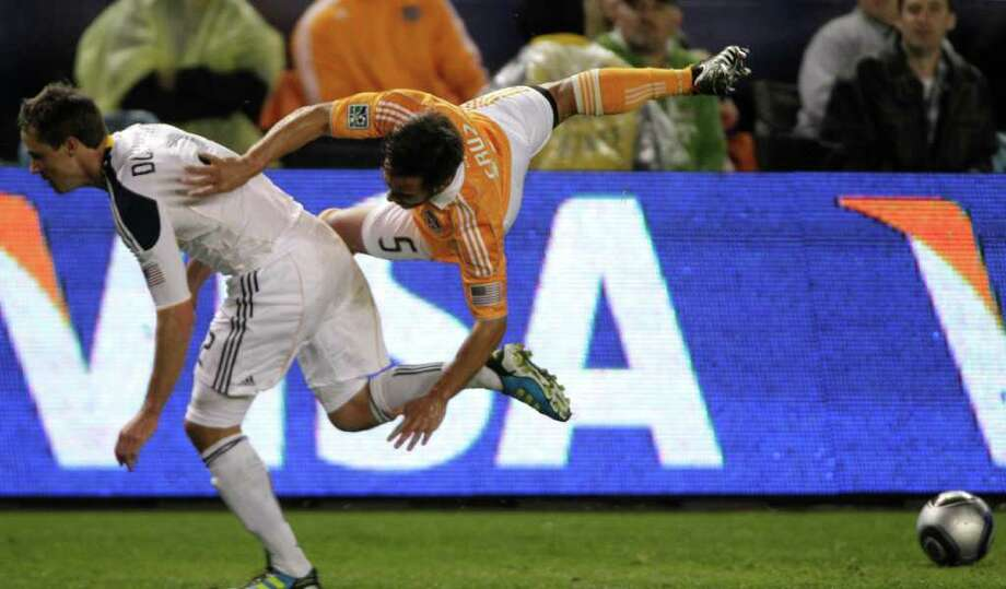 Houston Dynamo midfielder Danny Cruz (5) goes flying agains Los Angeles Galaxy defender Todd Dunivant (2) during the first half of the MLS Cup soccer match at the Home Depot Center Sunday, Nov. 20, 2011, in Carson, Calif. Photo: Brett Coomer, Houston Chronicle / © 2011 Houston Chronicle
