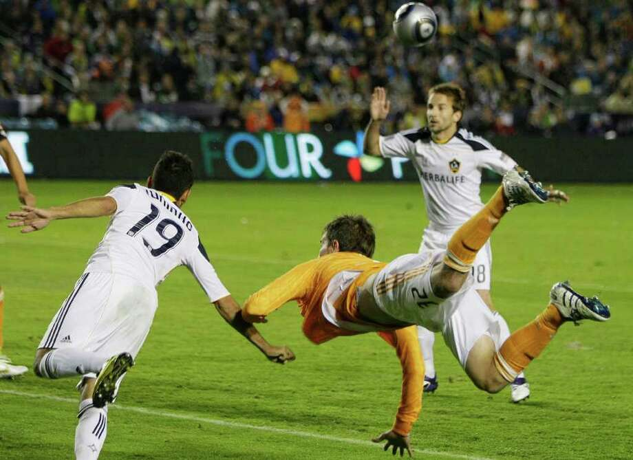 Houston Dynamo defender Bobby Boswell (32) dives for a ball against Los Angeles Galaxy midfielder Juninho (19) and forward Mike Magee (18) during the first half of the MLS Cup soccer match at the Home Depot Center Sunday, Nov. 20, 2011, in Carson, Calif. Photo: Brett Coomer, Houston Chronicle / © 2011 Houston Chronicle