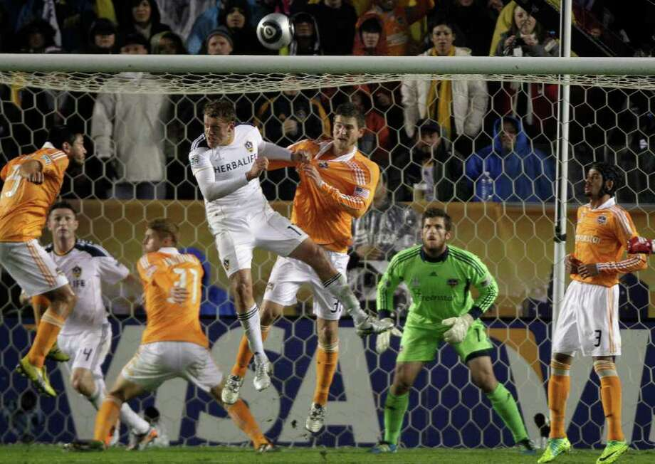 Los Angeles Galaxy forward Adam Cristman (17) and Houston Dynamo defender Bobby Boswell (32) fight for a header in front of goalkeeper Tally Hall (1) during the first half of the MLS Cup soccer match at the Home Depot Center Sunday, Nov. 20, 2011, in Carson, Calif. Photo: Brett Coomer, Houston Chronicle / © 2011 Houston Chronicle