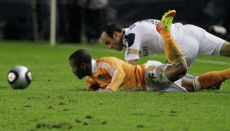 Houston Dynamo midfielder Corey Ashe (26) takes a tumble in a collision with Los Angeles Galaxy forward Landon Donovan (10) during the first half of the MLS Cup soccer match at the Home Depot Center Sunday, Nov. 20, 2011, in Carson, Calif. Photo: Brett Coomer, Houston Chronicle / © 2011 Houston Chronicle