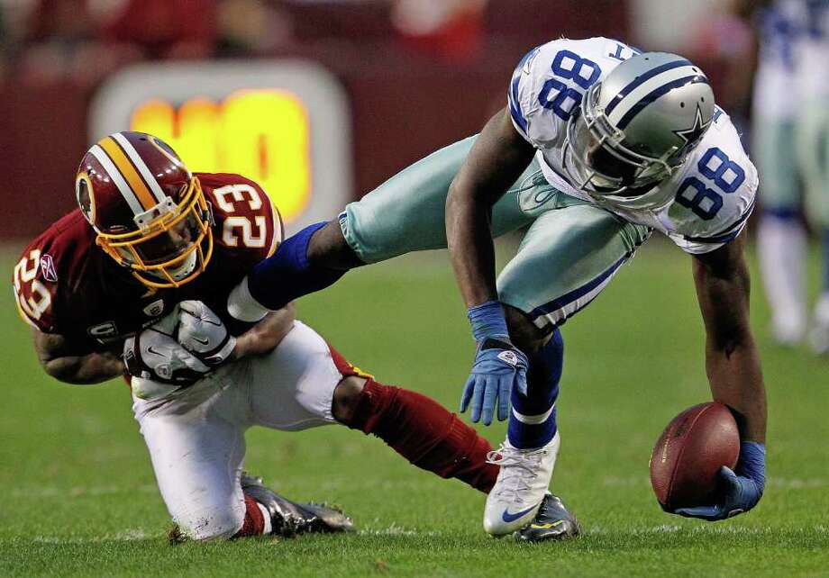 PABLO MARTINEZ MONSIVAIS: ASSOCIATED PRESS ANKLE TACKLE: Redskins cornerback DeAngelo Hall won't let go of Cowboys receiver Dez Bryant during overtime Sunday. But Bryant got away enough to catch three passes for 68 yards and a first-quarter touchdown. Photo: Pablo Martinez Monsivais / AP