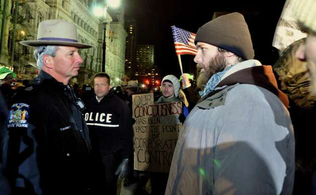 Andrew Fenewick, right, an Occupy Albany protester, faces off with New York State Troopers, moments before he was arrested, as were several other protesters who violated an 11pm curfew in state-run Lafayette Park which is located across Washington Avenue from the New York State Capitol, Albany, New York, Saturday, Nov. 19, 2011. (AP Photo/Stewart Cairns) Photo: Stewart Cairns