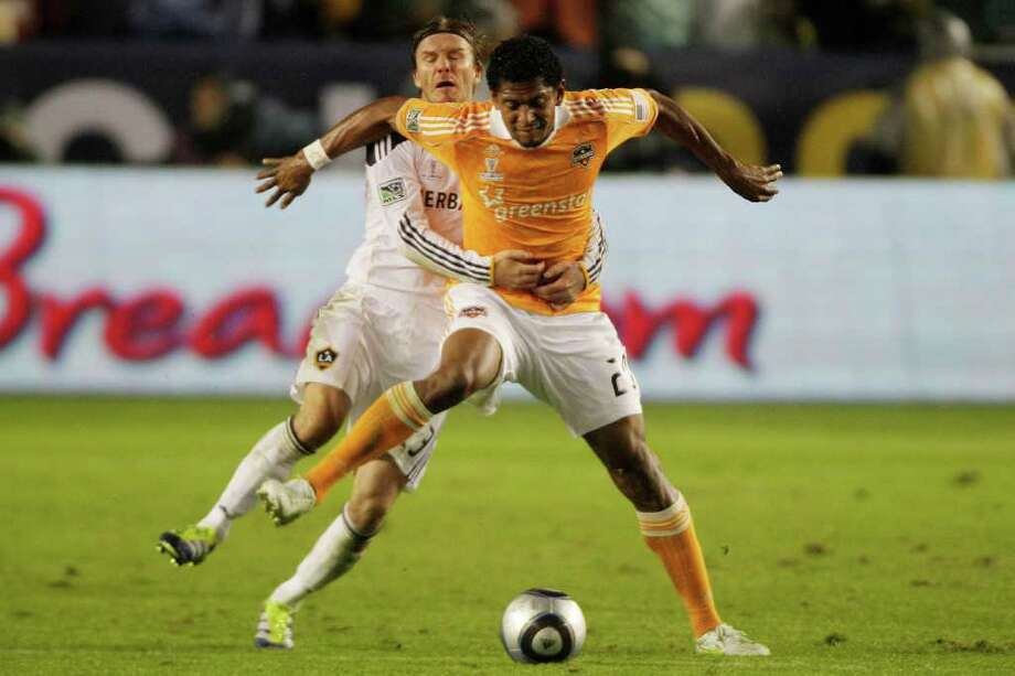 BRETT COOMER: CHRONICLE TUG OF WAR: The Galaxy's David Beckham, rear, tries to impede the Dynamo's Carlo Costly during the second half of the MLS Cup on Sunday night. Photo: Brett Coomer / © 2011 Houston Chronicle