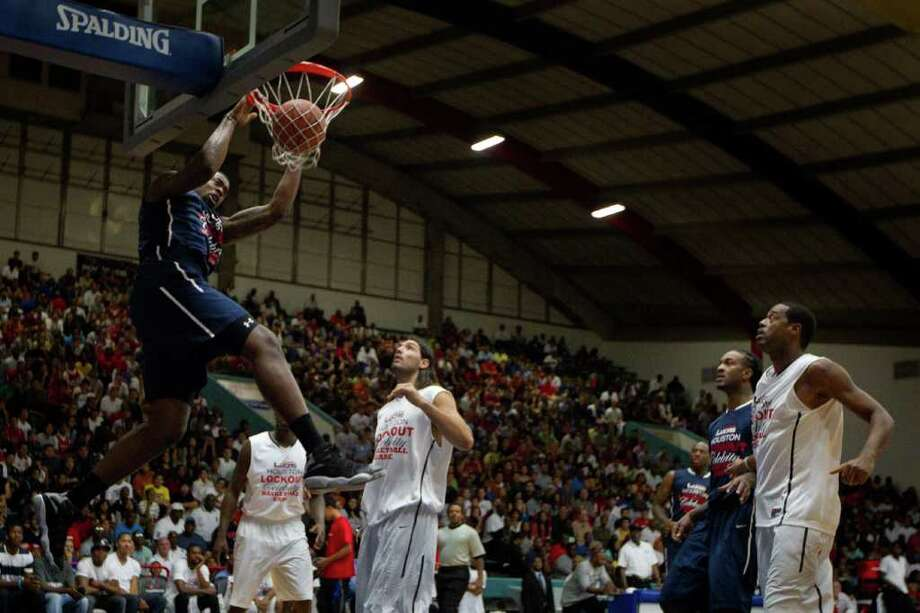 DeAndre Jordan of the Los Angeles Clippers slam dunks past Luis Scola of the Houston Rockets during the Houston Lockout Celebrity Basketball Game game at Delmar Fieldhouse on Sunday, Nov. 20, 2011, in Houston. Photo: Smiley N. Pool, Houston Chronicle / © 2011  Houston Chronicle