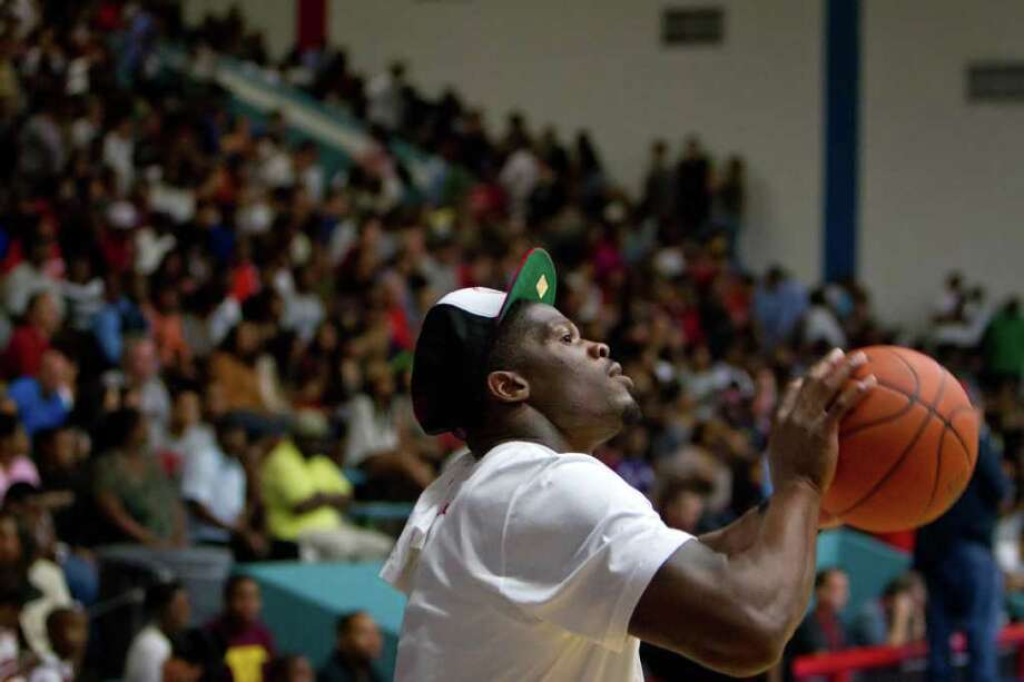 Houston Texans wide receiver Andre Johnson shoots baskets while the teams warm up before the Houston Lockout Celebrity Basketball Game game at Delmar Fieldhouse on Sunday, Nov. 20, 2011, in Houston. Johnson watched from the bench as he sat with the NBA players during the game. Photo: Smiley N. Pool, Houston Chronicle / © 2011  Houston Chronicle