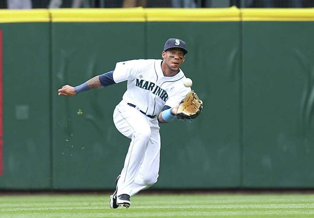 Left fielder Greg Halman of the Seattle Mariners makes a running catch on a ball hit by Ben Francisco  of the Philadelphia Phillies to end the first inning at Safeco Field on June 19, 2011 in Seattle.