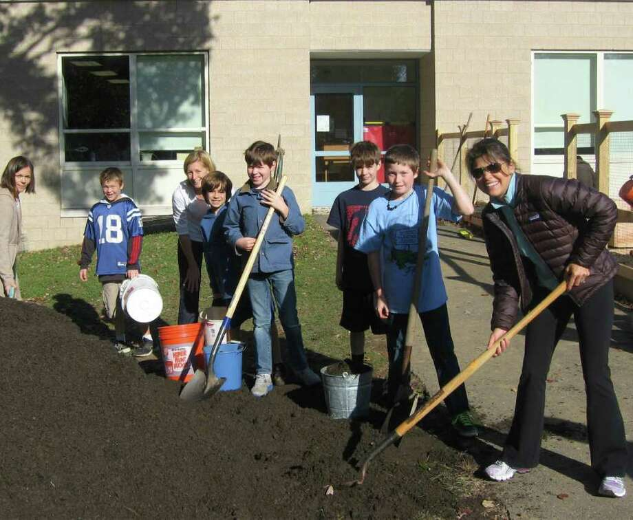 Michelle Sini (PTO vice chairman), Cole Anderson, Kristin Collier (PTO green team chairman), Paul Ridder, Thomas Finnegan, Liam Roach, Sam Smith, and Sharon Patricelli (PTO co-chairman) fill buckets with soil to transfer into the planting beds. Photo: Contributed Photo