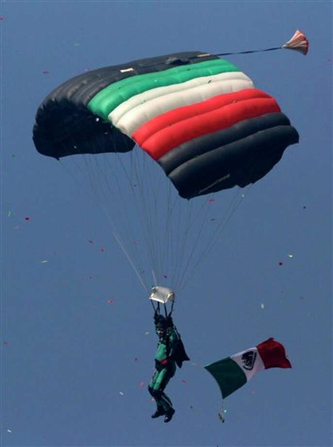 A paratrooper glides during Mexican Revolution 101th anniversary celebrations in Mexico City's Zocalo plaza, Sunday Nov. 20, 2011. Mexico marks 101 years since the seven-year conflict began on Nov. 20, 1910 that saw peasant armies led by heroes Emiliano Zapata and Pancho Villa topple the dictatorship of Porfirio Diaz. (AP Photo/Marco Ugarte) Photo: Associated Press