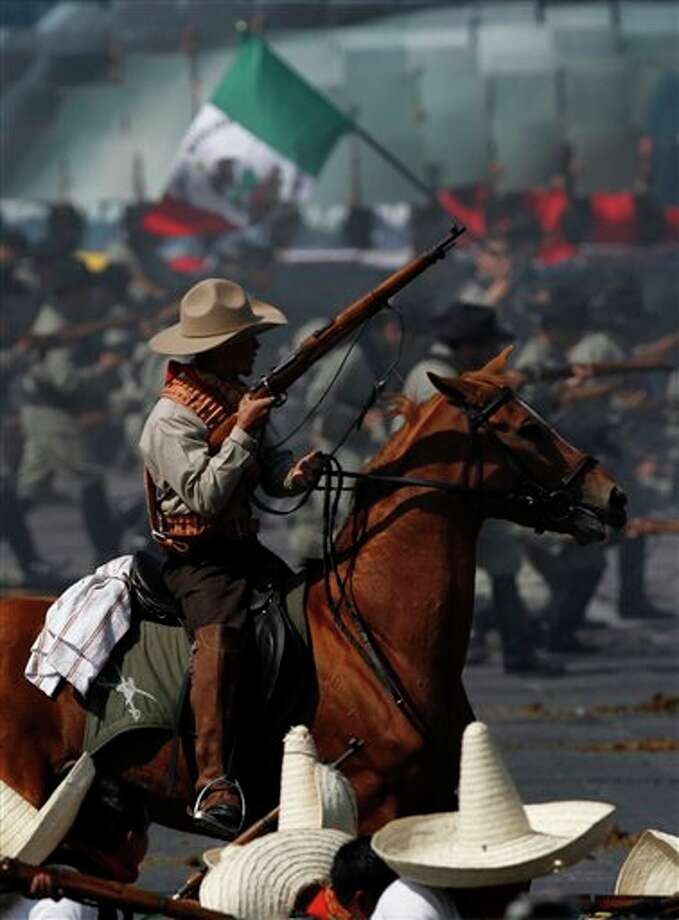 **  CORRECTS YEAR  ** Soldiers re-enact a revolution battle as part of Mexican Revolution 101th anniversary celebrations in Mexico City's Zocalo plaza, Sunday Nov. 20, 2011. Mexico marks 101 years since the seven-year conflict began on Nov. 20, 1910 that saw peasant armies led by heroes Emiliano Zapata and Pancho Villa topple the dictatorship of Porfirio Diaz. (AP Photo/Marco Ugarte) Photo: Associated Press