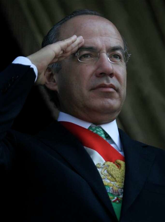 **  CORRECTS YEAR  ** Mexico's President Felipe Calderon salutes as he attends a parade commemorating the 101 anniversary of the Mexican Revolution in Mexico City's Zocalo plaza, Sunday Nov. 20, 2011. Mexico marks 101 years since the seven-year conflict began on Nov. 20, 1910 that saw peasant armies led by heroes Emiliano Zapata and Pancho Villa topple the dictatorship of Porfirio Diaz. (AP Photo/Marco Ugarte) Photo: Associated Press