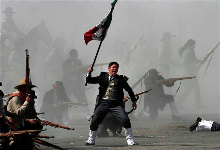 Soldiers re-enact a revolution battle as part of Mexican Revolution 101th anniversary celebrations in Mexico City's Zocalo plaza, Sunday Nov. 20, 2011. Mexico marks 101 years since the seven-year conflict began on Nov. 20, 1910 that saw peasant armies led by heroes Emiliano Zapata and Pancho Villa topple the dictatorship of Porfirio Diaz. (AP Photo/Marco Ugarte) Photo: Associated Press