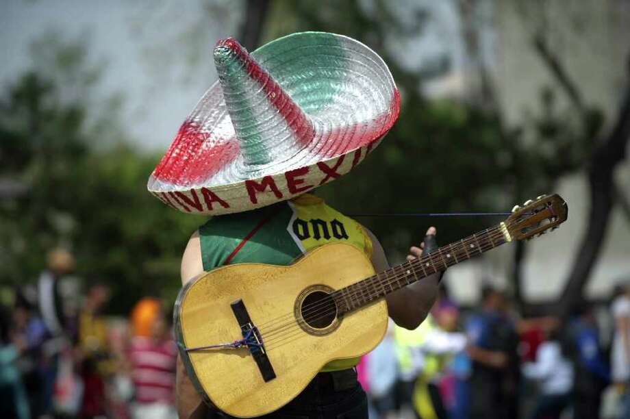 A man using a traditional Mexican hat, holds his guitar as he observes a military parade commemorating the 101th anniversary of the Mexican Revolution along Reforma Avenue on November 20, 2011 in Mexico City.  AFP PHOTO/Yuri CORTEZ Photo: YURI CORTEZ, Getty Images / 2011 AFP