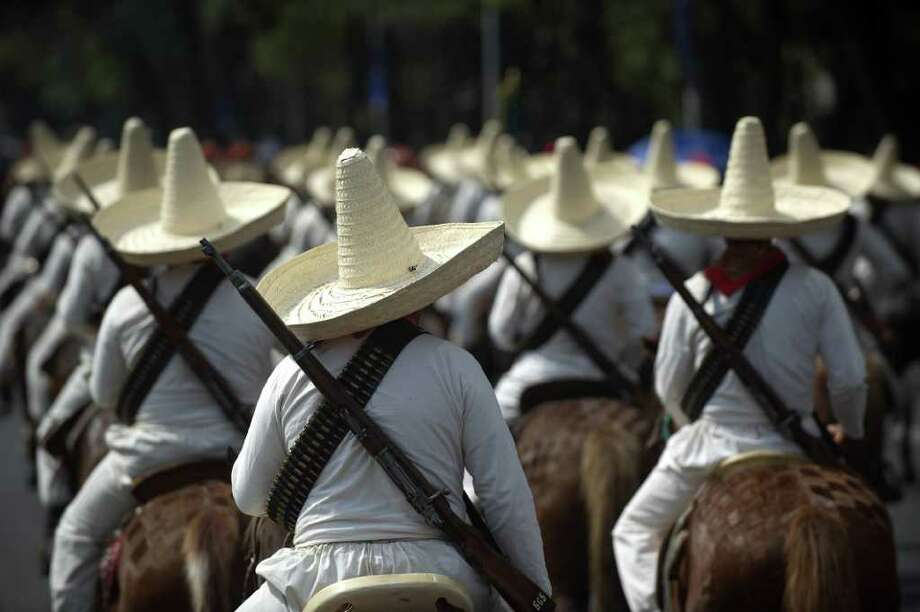 Men dressed as revolutionaries perform during a military parade commemorating the 101th anniversary of the Mexican Revolution along Reforma Avenue on November 20, 2011 in Mexico City.  AFP PHOTO/Yuri CORTEZ Photo: YURI CORTEZ, Getty Images / 2011 AFP